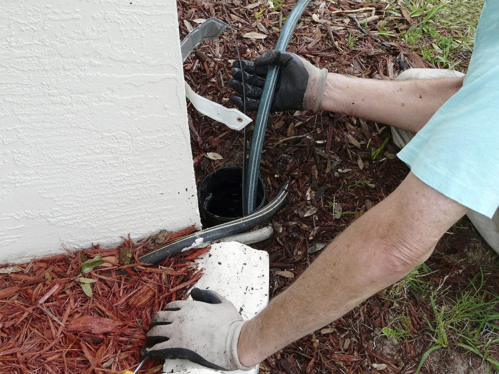 Homeowner using a sewer snake in outside drain