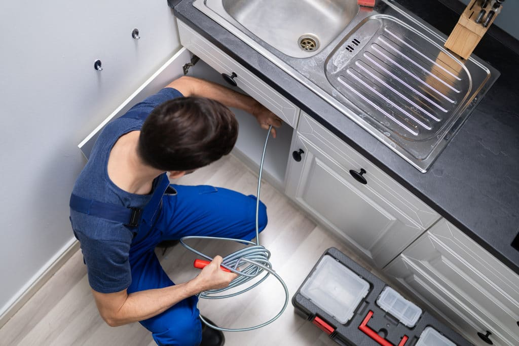 Male Plumber Cleaning Clogged Drain