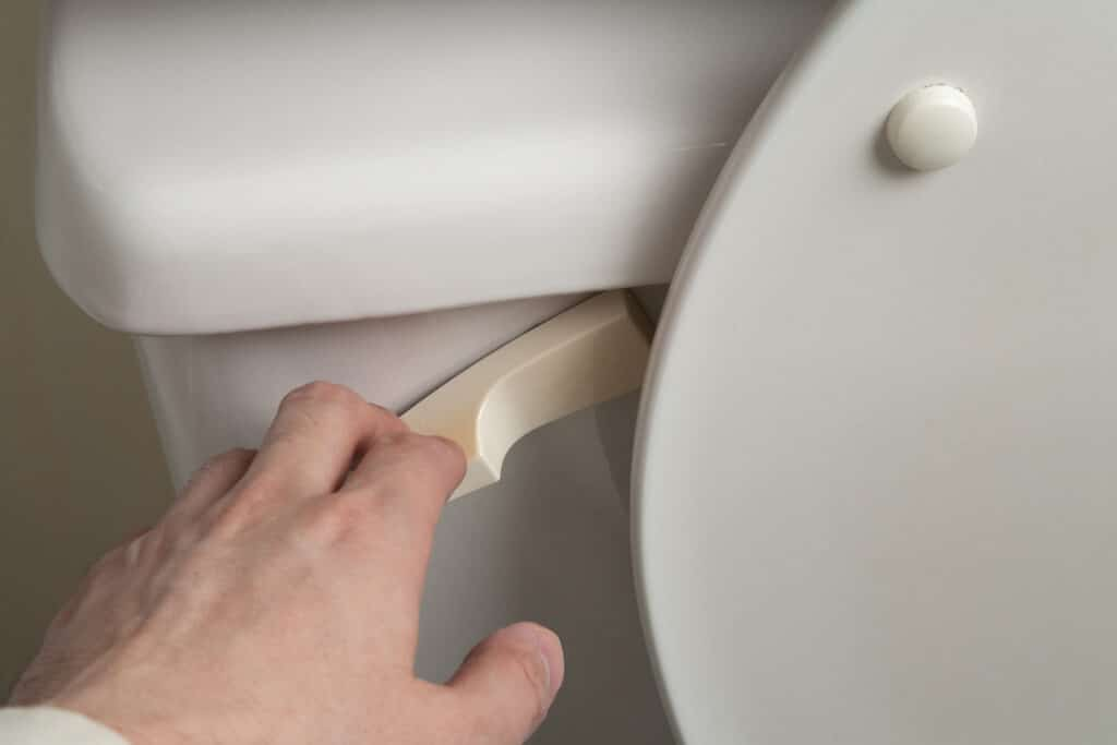 closeup of a toilet handle being pulled